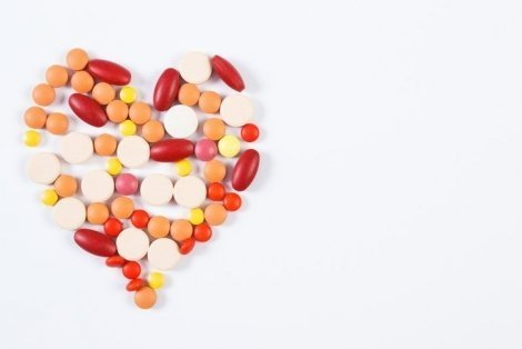 Heart shaped medical pills and capsules on white background